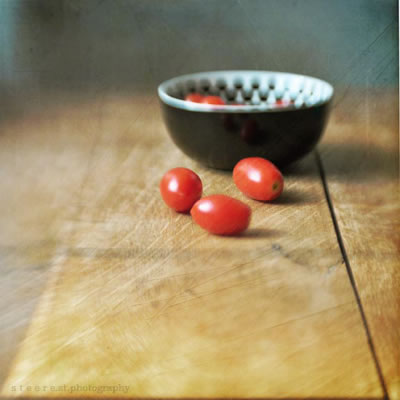Three cherry tomatoes on countertop outside a bowl with others