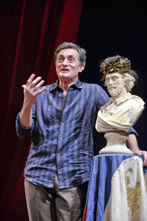 Roger Rees talks while standing next to a bust of Shakespeare wearing a crown